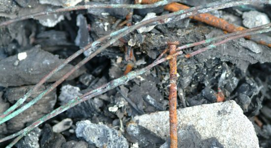 A nail driven threw an electrical conductor caused arcing between the nail & the conductor starting the fire sequence.
